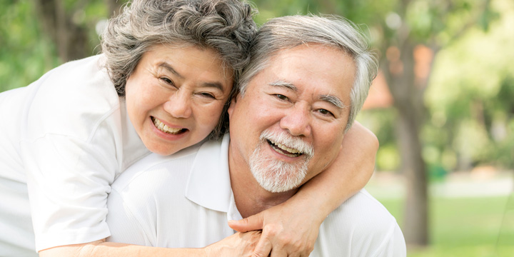 Smiling older woman behind smiling older man embracing him with her head resting on his shoulder