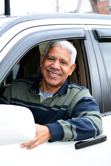 Smiling older man wearing a blue-and-green-striped collared shirt sitting in a car and leaning one arm out the open window