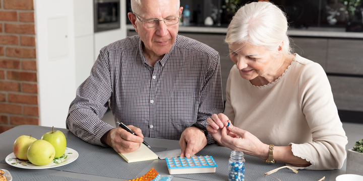 Older man and woman sitting together at a kitchen table sorting pills into a box and making notes on a yellow pad