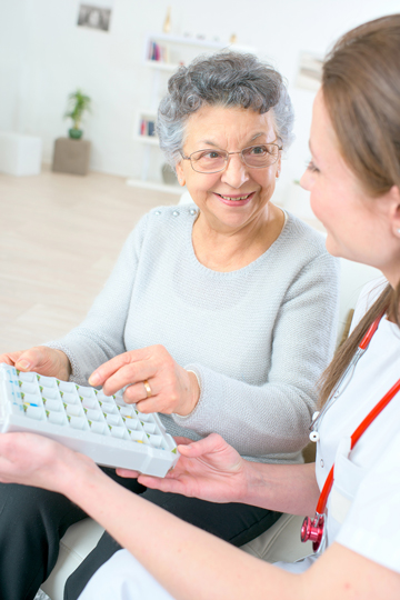 Smiling older woman with grey hair and glasses reaching for a pillbox being handed to her by a young healthcare professional