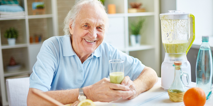 Smiling older man holding a glass of green smoothie while sitting next to the blender that was used to make it