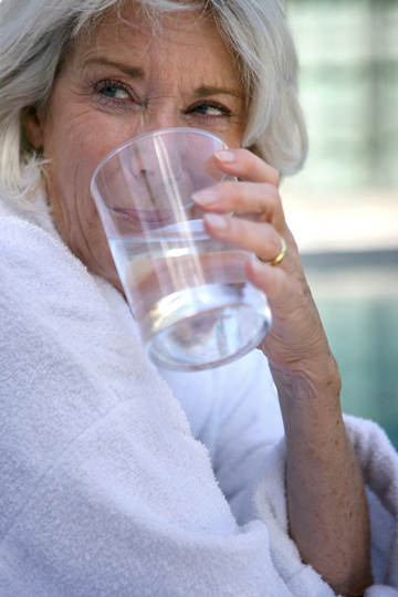 Older woman in a white bathrobe drinking water from a clear glass and smiling while looking off to the side