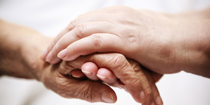 An older person's hand being held by the two hands of someone younger