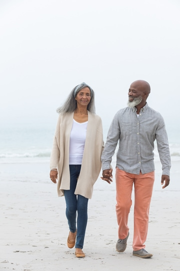 Smiling older couple holding hands, wearing long-sleeved shirts and pants, and walking on a sandy ocean beach