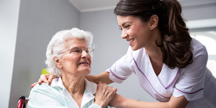 Smiling woman in a medical uniform leaning forward to embrace an older woman who is sitting in a wheelchair