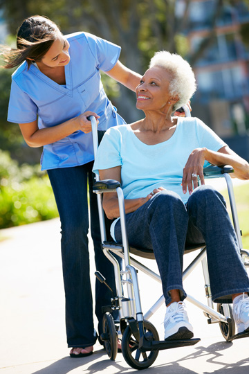 Older woman in a wheelchair looking over her shoulder to smile at a woman in medical scrubs who is pushing the wheelchair