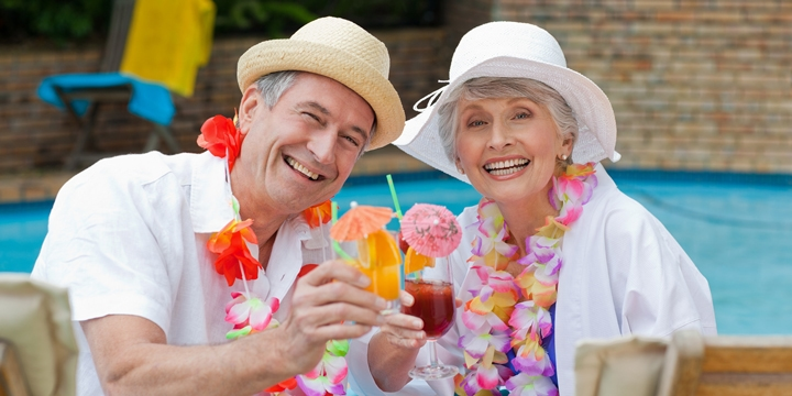 Smiling older couple sitting by a pool wearing hats and flower necklaces while holding drinks with little umbrellas in them