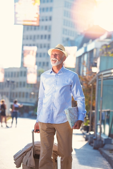 Smiling man with a grey beard and a hat standing on a city street holding a map and pulling a rolling suitcase