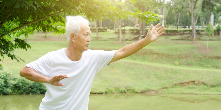 Older man in loose white clothing doing tai chi in a park, leaning slightly forward with one arm extended