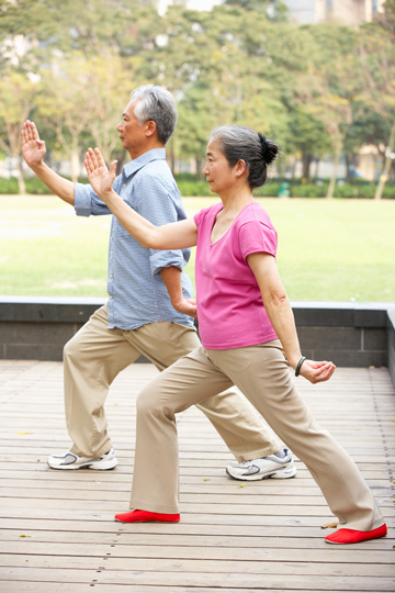 Older man and woman practicing tai chi, each with one foot forward under a bent front knee and one arm raised at an angle