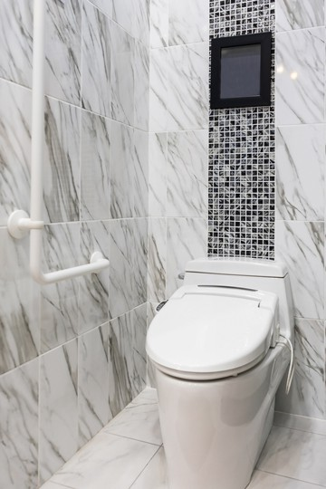 A closed toilet next to a grab bar in a bathroom with black and white marble tiles