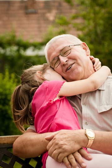 Young girl in a pink shirt hugging a smiling older man with eyeglasses while they sit on a bench outside